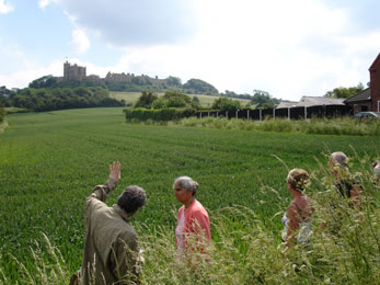 rupert clamp talking to walk participants pointing to bolsover castle in distance with green feild of unknown crops infront