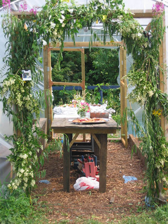 poly tunnel decorated with folliage, with wooden table and food in centre