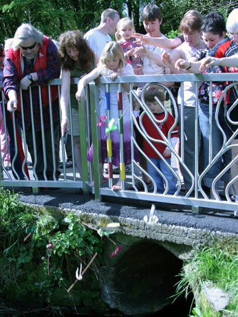 Image of people playing pooh sticks at launch of Bridge