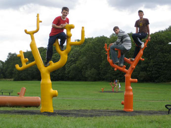 Image of tree scultures with youths climbing/sitting on them