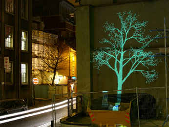 photograph of projected tree on outside of broadway building with street visible and skip infront