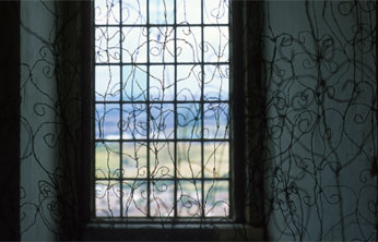multiple twisted wire drawings of decorative iron fencework hung infront of narrow leaded window of castlecastle