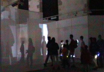 audience wandering around chapel - their shadows projected onto voile screens