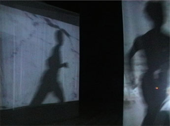 dancer running past screens with projected video & shadow reflected in large mirror