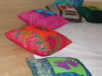 cushions made by Rosie Hobbs using the womens textile work - handmade felt hands and feet embroidered with beads