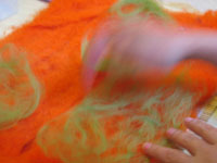 blurred hand in motion making orange & green felt