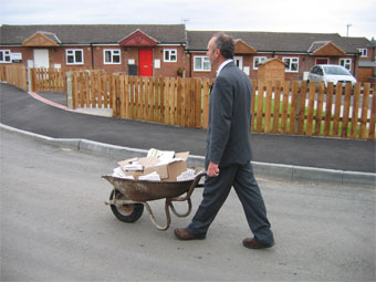 Ian Thorley dressed in suit pushing a wheel barrow around the estate with plaques and invites to creative consultation event